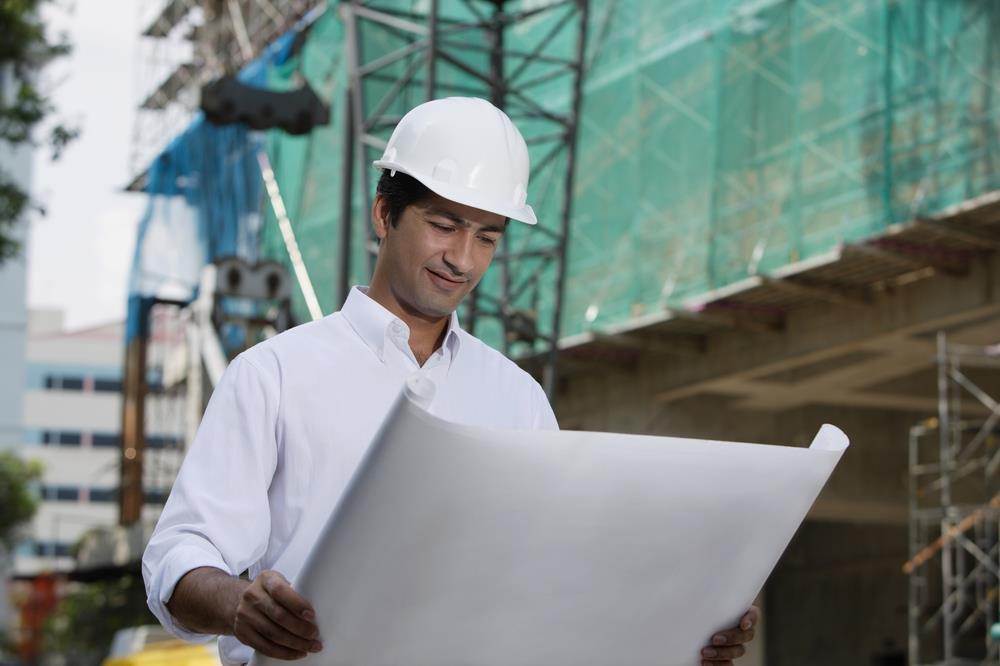 construction executive reviewing blueprints at a job site