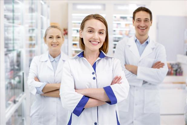 happy pharmacy manager standing in front of her two happy pharmacy employees