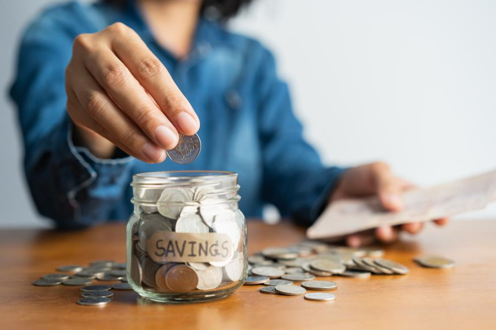 Woman putting money in savings jar