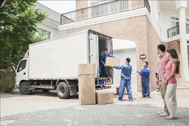 couple supervising movers unloading boxes from a truck
