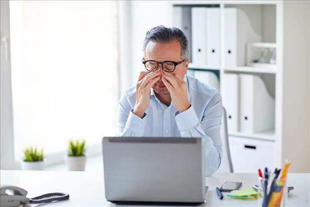 Dissapointed man sitting at desk after not getting raise
