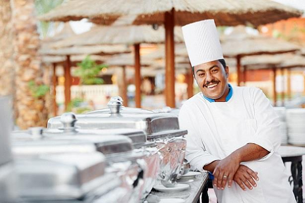 Happy chef posing in front of buffet at a tropical resort