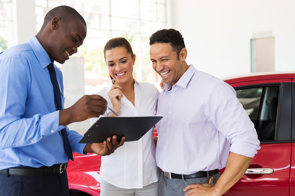 car salesperson going over details with his clients
