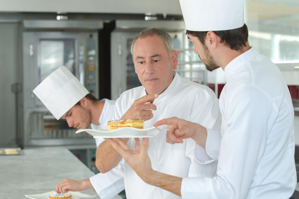 Culinary instructor teaching a chef student