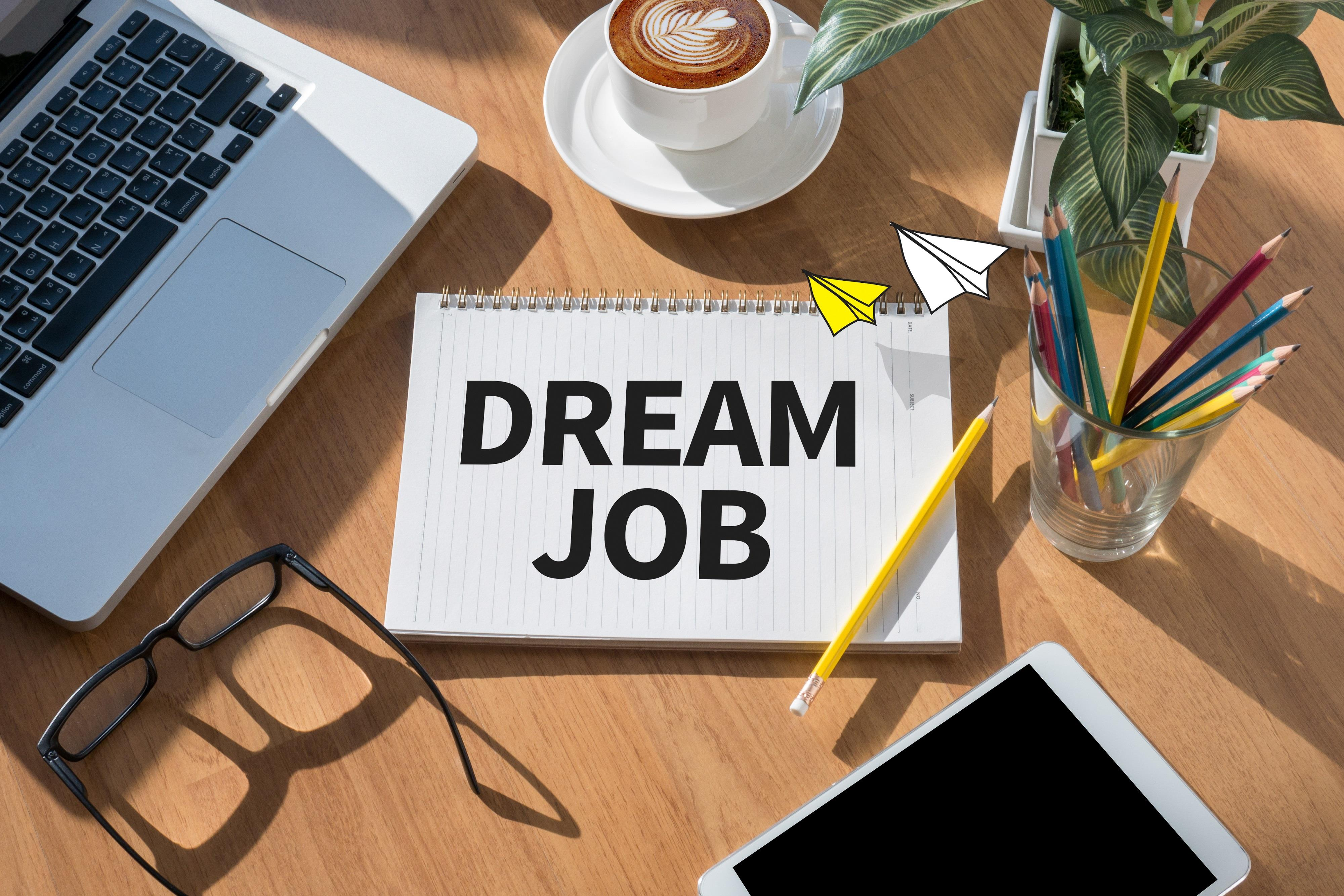 "desk with the words ""dream job"" on a notebook"