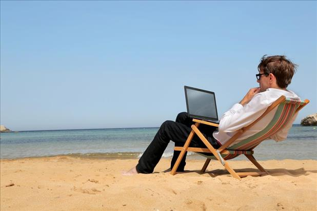 Man at the beach searching for jobs on his laptop