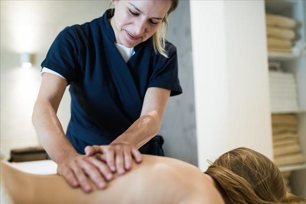 massage therapist giving back massage to client