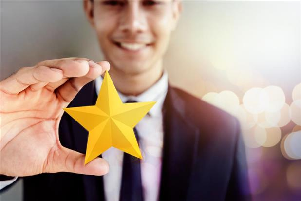 employee holding up a gold star