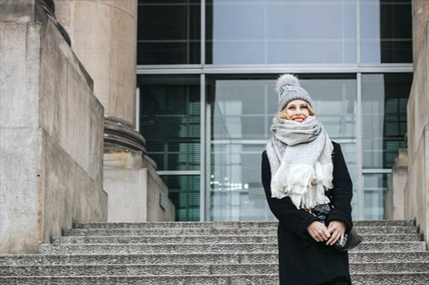 Young woman wearing stocking cap and heavy scarf for winter job interview