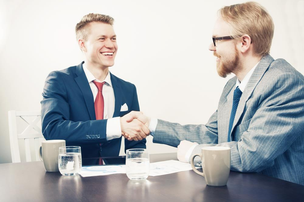 sales professional closing a deal with a client and shaking his hand