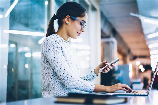 Woman checking phone while working on computer