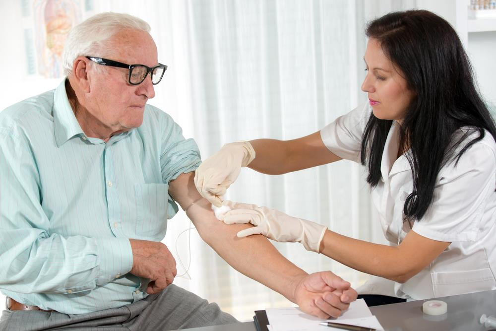 phlebotomist drawing blood from an elderly patient