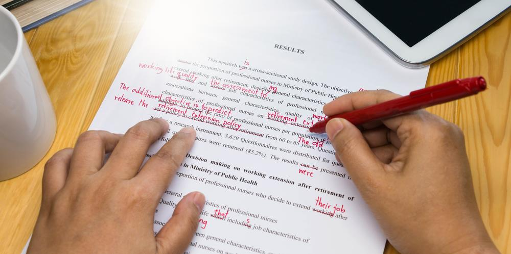closeup of a proofreader using their red pen to mark errors on a document