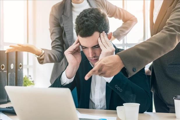 Man stressing while two people give him instructions
