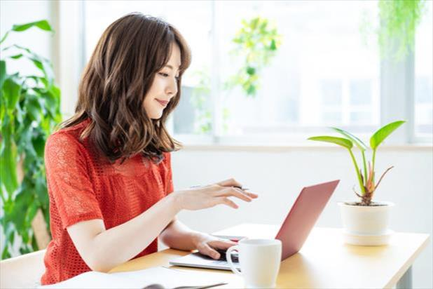 woman looking at a laptop while working from home