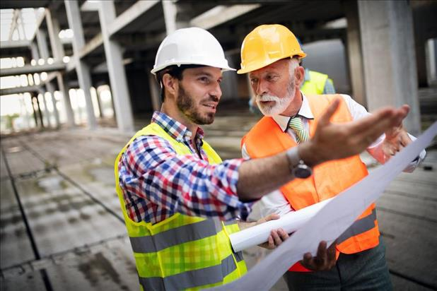 Older construction professional with younger employee on job site