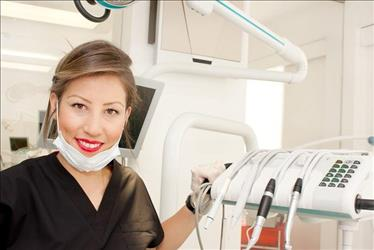 Dentist posing in front of machinery in examination room