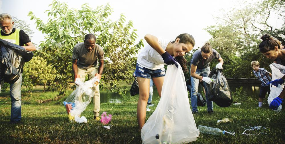 group of employees volunteering to pick up trash at a park
