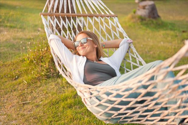 woman relaxing in her hammock while taking a staycation at home