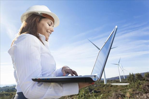 female environmental engineer in the field on her laptop with wind turbines in the background