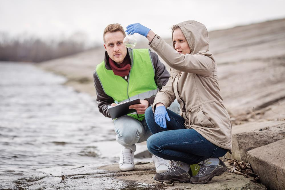 female environmental scientist testing river water with her male partner taking notes