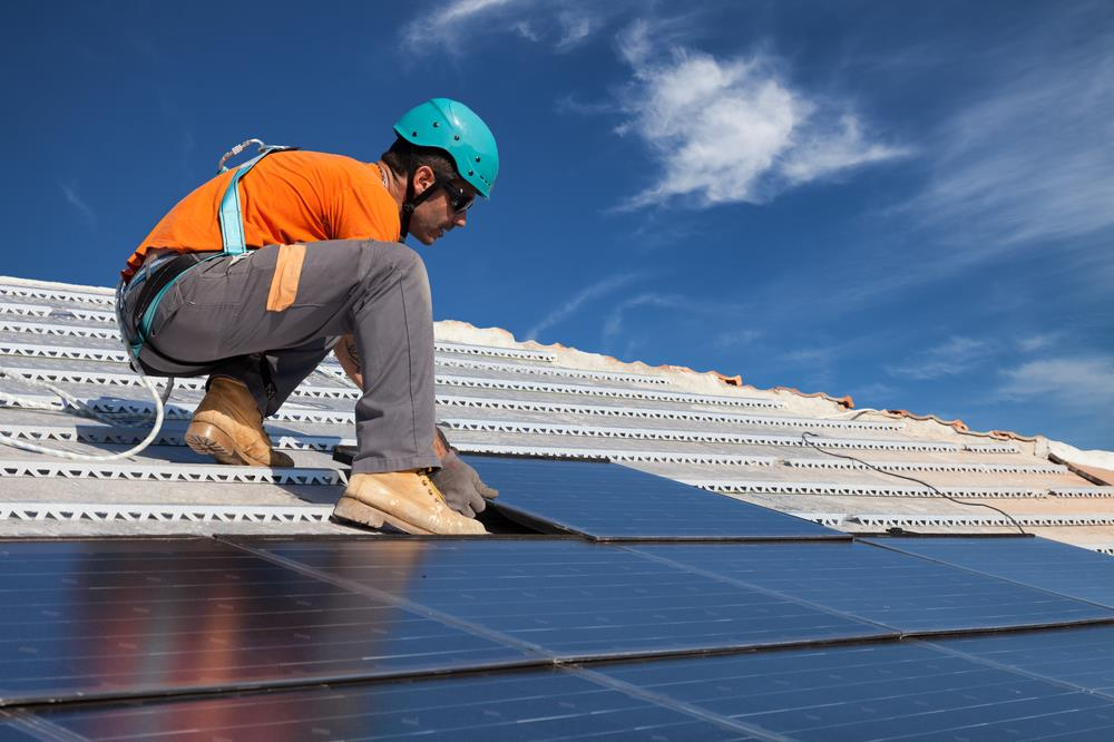 solar photovoltaic installer working on a rooftop