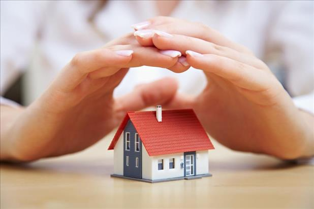 insurance agent's hands over a small house
