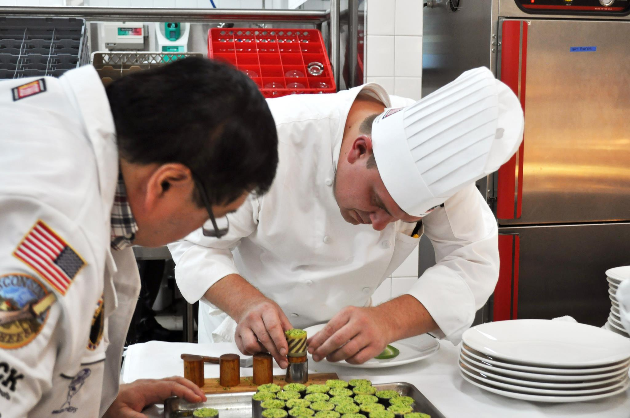 two acf chefs creating a dish in the kitchen