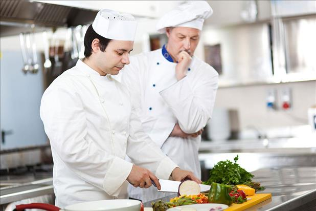 Culinary student training to become a chef and learning knife skills in the kitchen