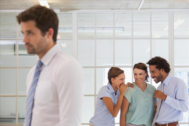 Group of professionals gossiping behind their coworker's back