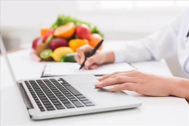 Closeup shot of dietitian writing their resume with fresh fruit in the background
