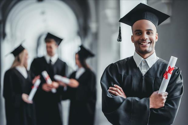 College graduate in robes posing for a photo