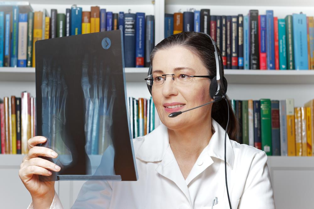 radiologist working remotely on the phone examining x-ray