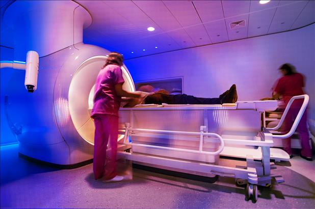 patient receiving an mri with help from two radiologic technoloigsts