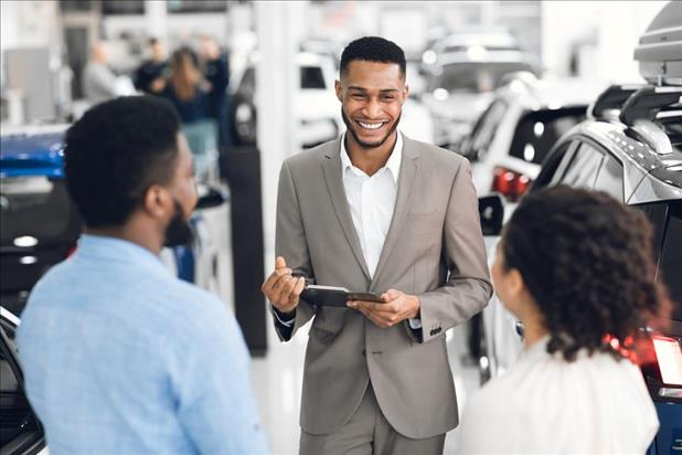 Automotive sales manager greeting customers