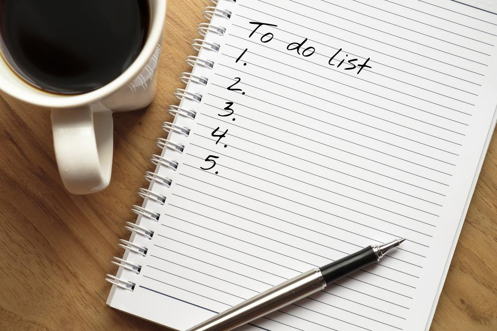 To-do list waiting to be filled out next to a cup of coffee