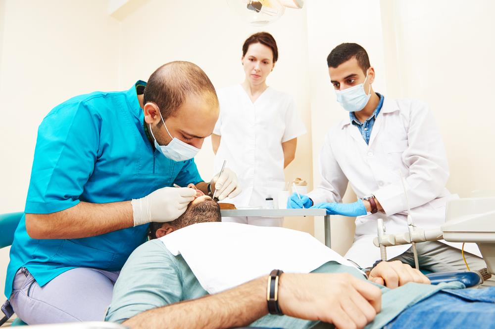 Dental instructor training students on how to perform a patient examination