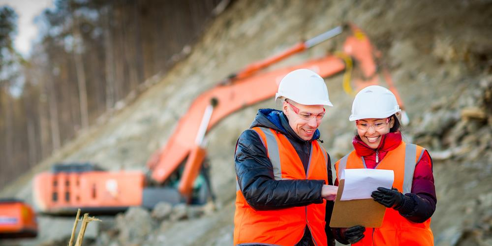 two construction team members reviewing a document on a job site
