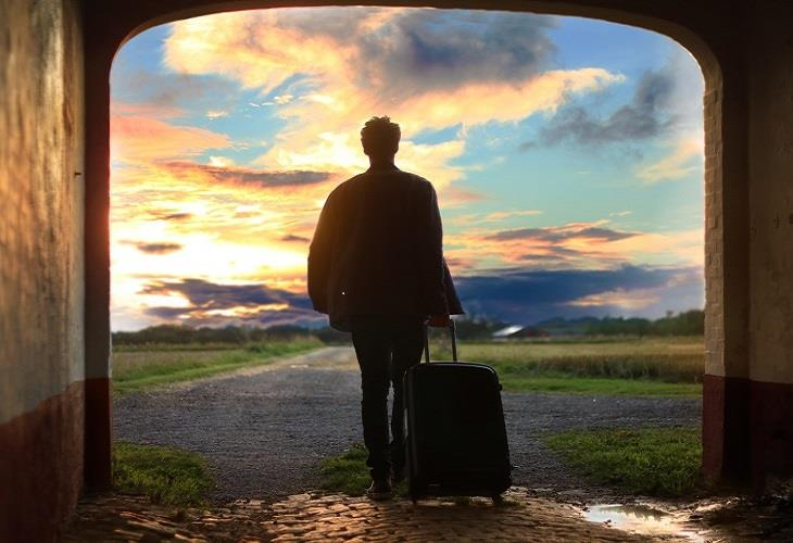 Man walking into sunset with suitcase