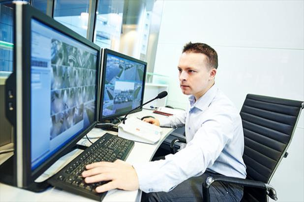 Surveillance officer sitting at security desk and monitoring video feeds