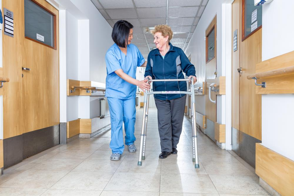 nurse assisting an elderly patient in a hospital hallway