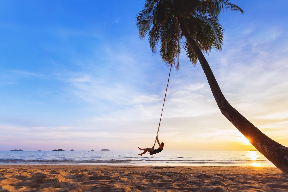 Young woman on a swing at the beach