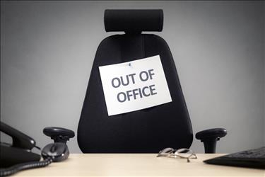 Empty desk chair with out of office sign