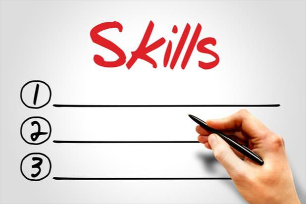 "hand writing writing a list under the word ""skills"""