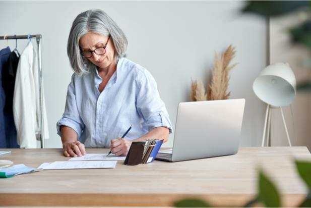older woman writing at a table