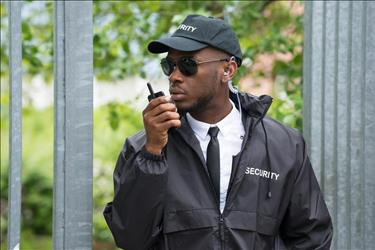 security guard patrolling outside with a two-way radio
