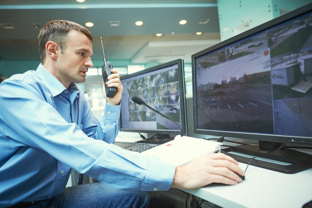 security officer with a two-way radio watching security camera footage on multiple computer monitors