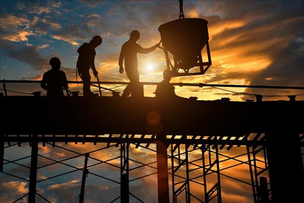 construction team working on site with a sunset in background