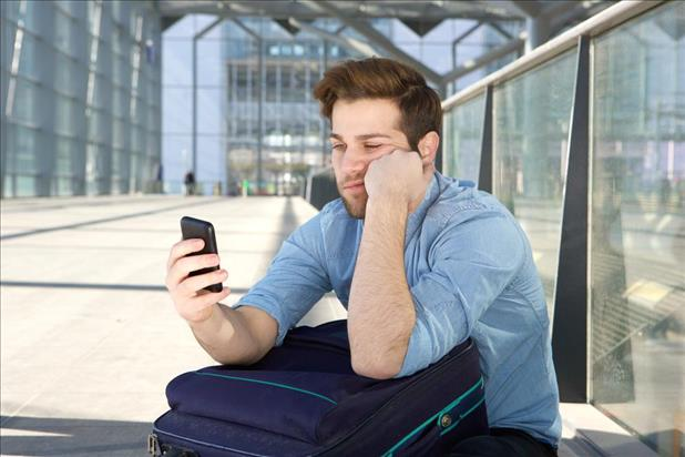 Frustrated man looking at phone, waiting for a call