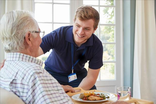 male home health aide helping a patient enjoy his meal
